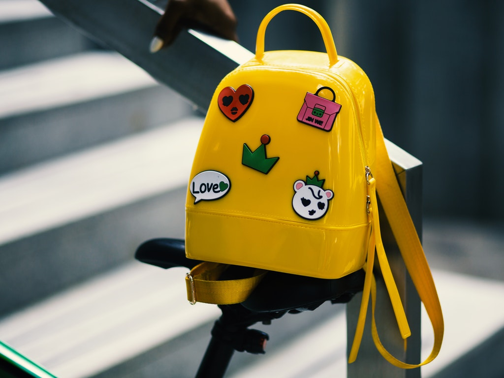 yellow-backpack-with-five-assorted-stickers-on-grey-metal-934673